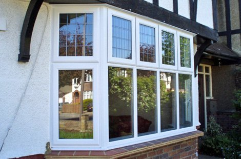 Rectangular bay windows on a white and black tudor style home.