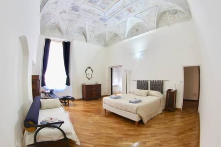 Camera matrimoniale con due letti e affreschi