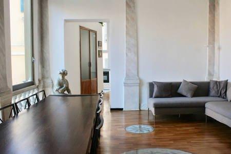 Stanza con  divano, parquet e marmi decorativi