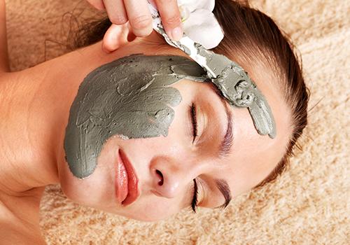 una mano che applica una maschera facciale a una ragazza