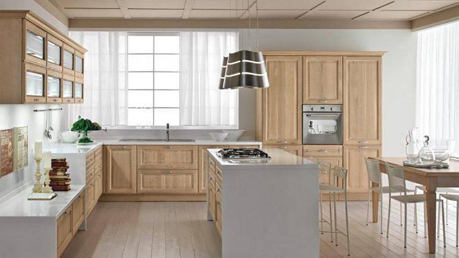 cucina con mobili e isola in legno chiaro e