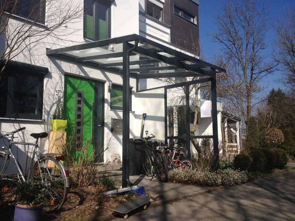 Haustürvordach aus Glas und Metall vor grüner Tür