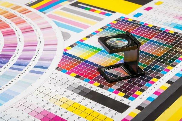 una lente di ingrandimento e delle stampe con degli esempi di colore