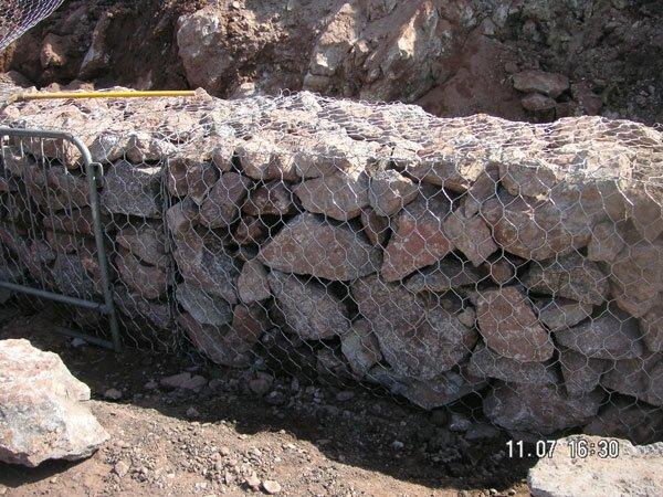 dei sassi e davanti una rete metallica