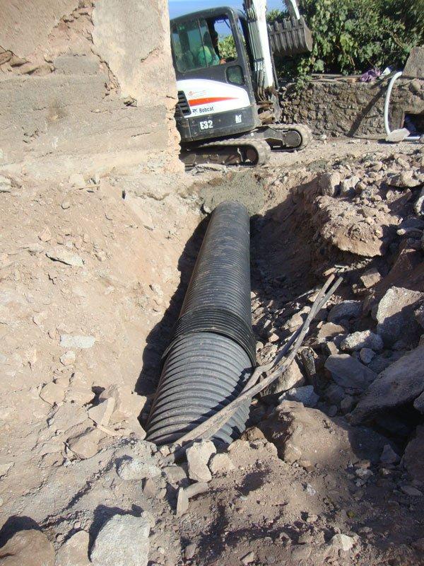 un tubo nero nel terreno, dei sassi e più avanti una scavatrice