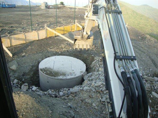 una scavatrice al lavoro in uno scavo