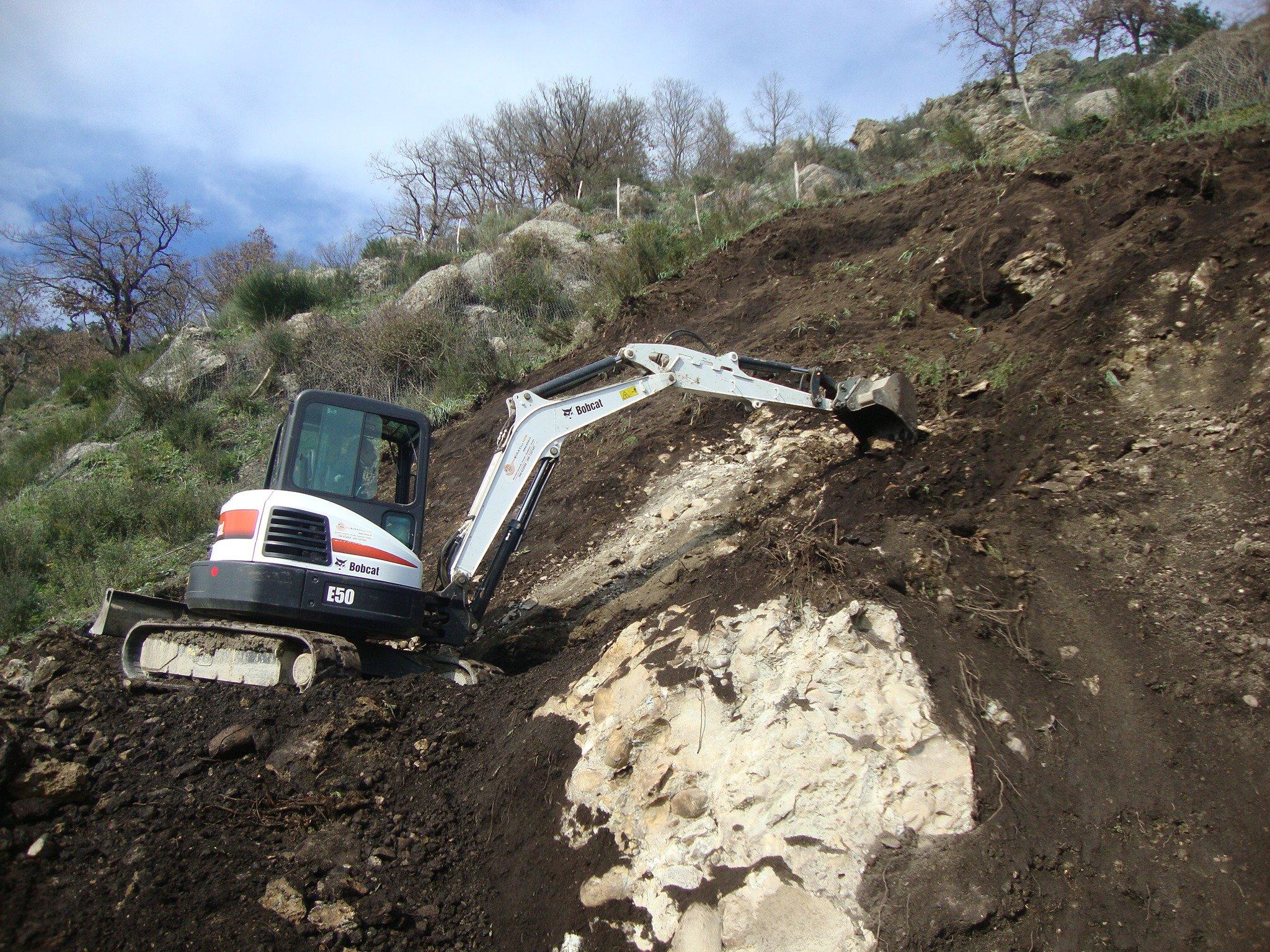 Un escavatore lavora sul movimento terra