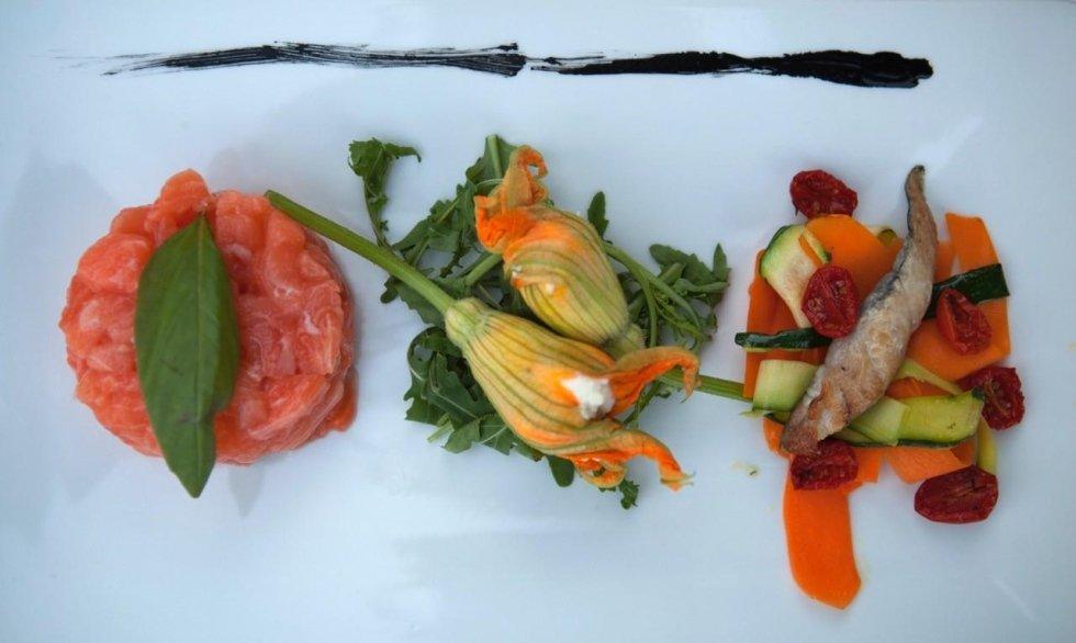 vista frontale di un piatto tartare di tonno, gamberi e fiori di zucca ripieni