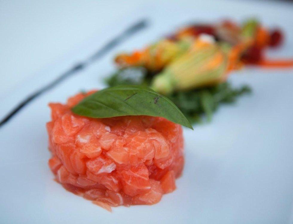 vista laterale di un piatto tartare di tonno, gamberi e fiori di zucca ripieni