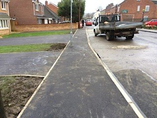 Tarmac paving and driveways in front of a row of houses
