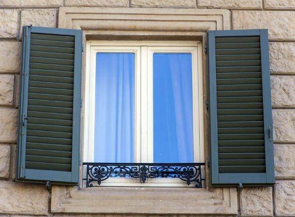una finestra aperta con alcune tende in sottofondo
