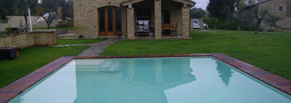 una piscina in un giardino e uno stabile in pietra