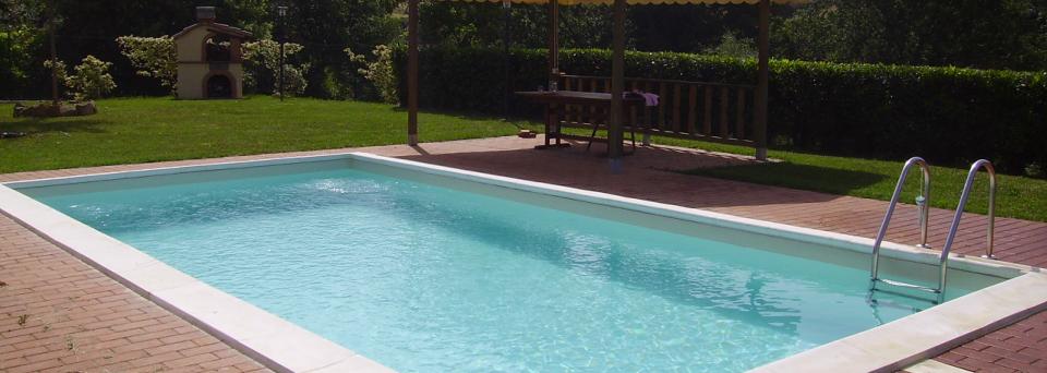 una piscina in un giardino con un gazebo e un barbecue