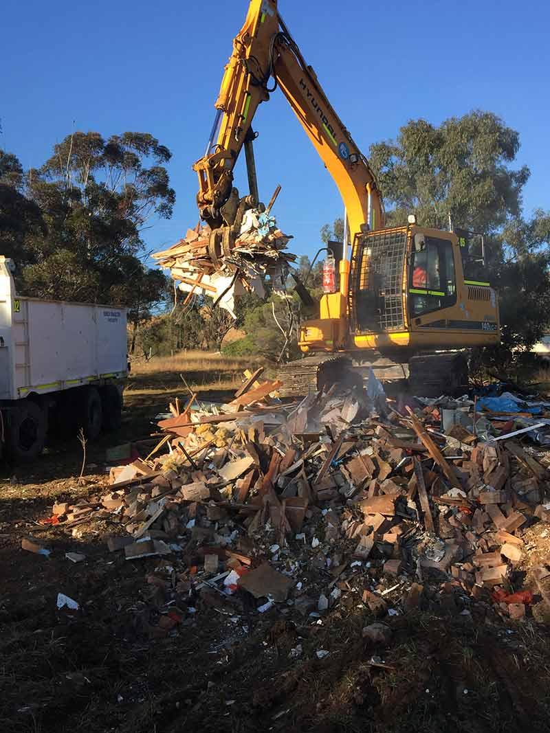 excavator on pile of rubble