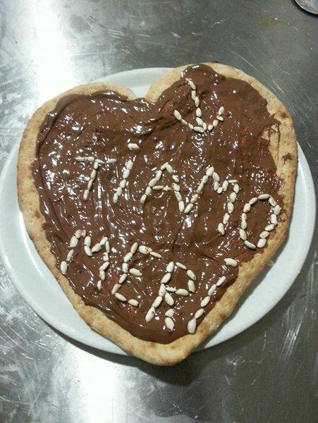 pasta di pizza guarnita con cioccolato e scritta TI AMO MERI