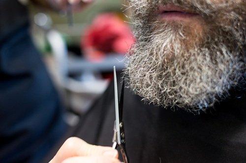 un barbiere che sfoltisce una barba