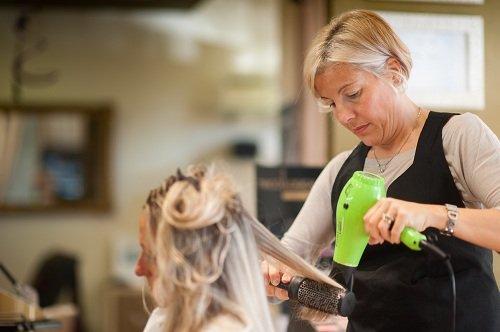 una parrucchiera che asciuga i capelli
