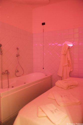 stanza con vasca da bagno e un lettino per trattamenti corpo di un centro estetico