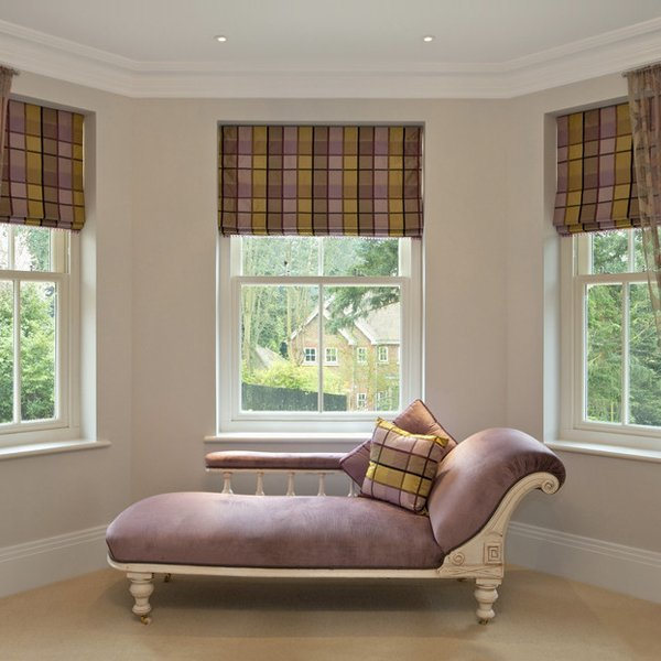 patterned roman blinds over 3 windows in a living space with a chaise lounge