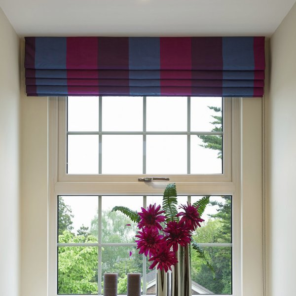 striped patterned roman blind over a window with flowers