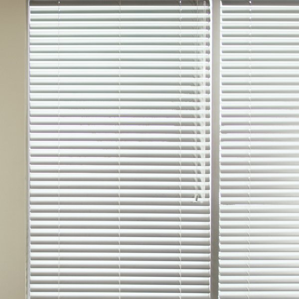 upvc white Venetian blind drawn over a window