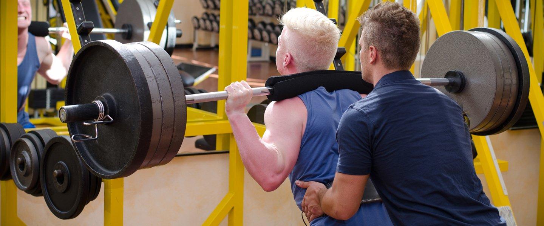 Sollevamento pesi con l'istruttore personale a Voghera
