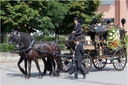 vista laterale di una carrozza trainata da cavalli per un rito funebre