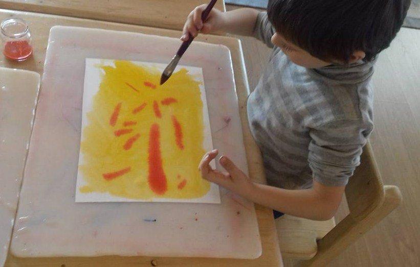 bambino mentre disegna con gli acquarelli