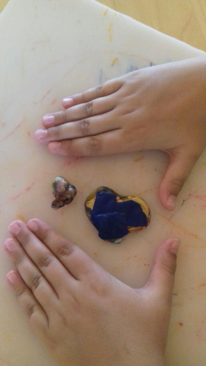 bambino che compone un pongo di colore blu e gialla