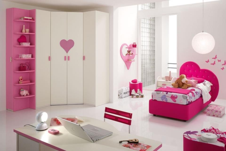 una  camera da bambina con un armadio, una scrivania e un letto con la testata a forma di cuore