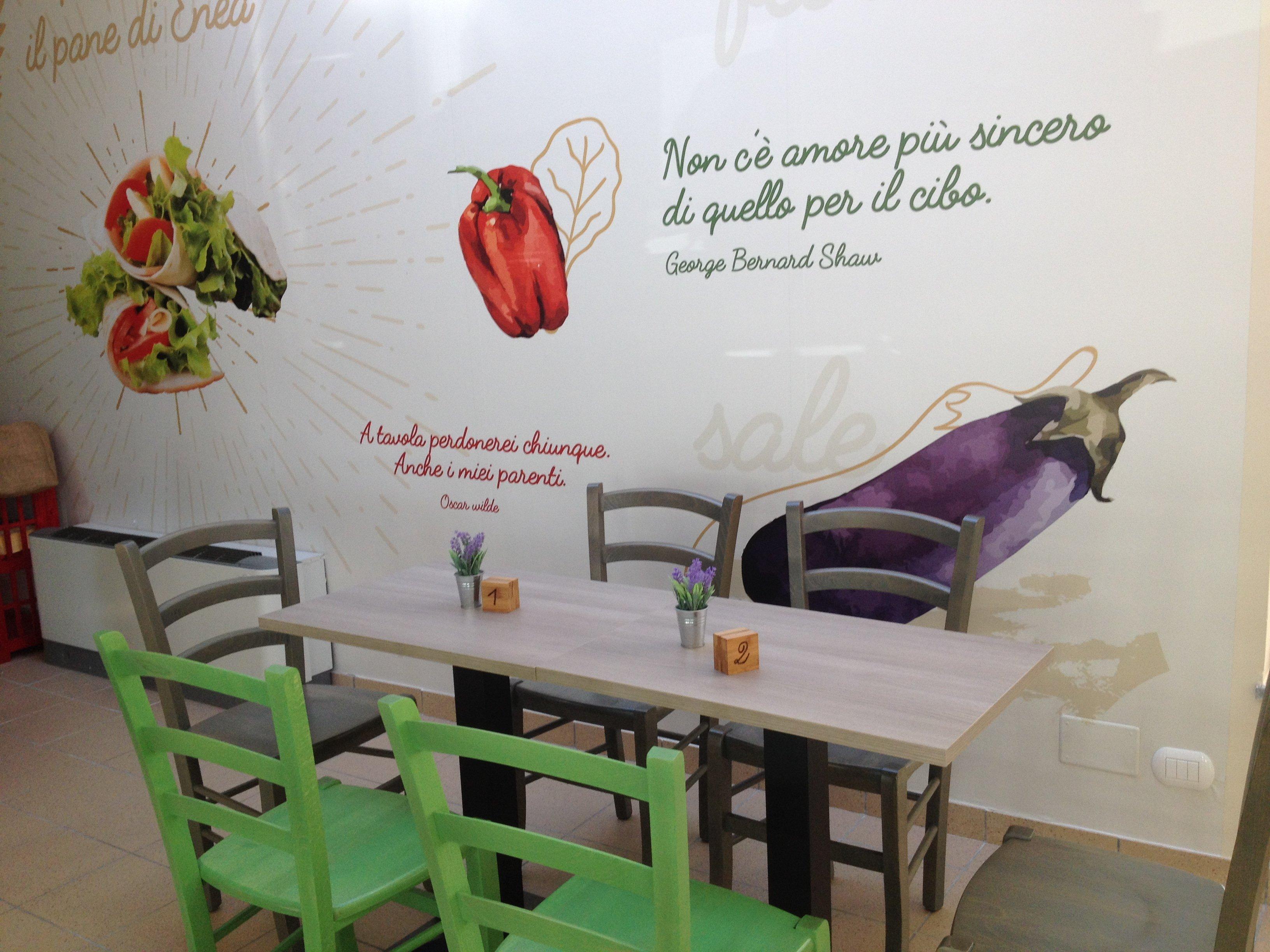 Sala interna della piadineria con sedie e tavoli colorati