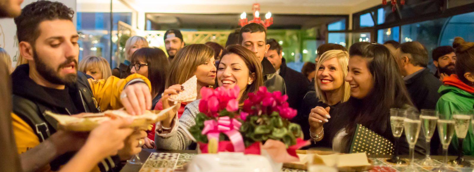 Una donna seduta al tavolo di Piada Mia mangia una piadina sorridendo