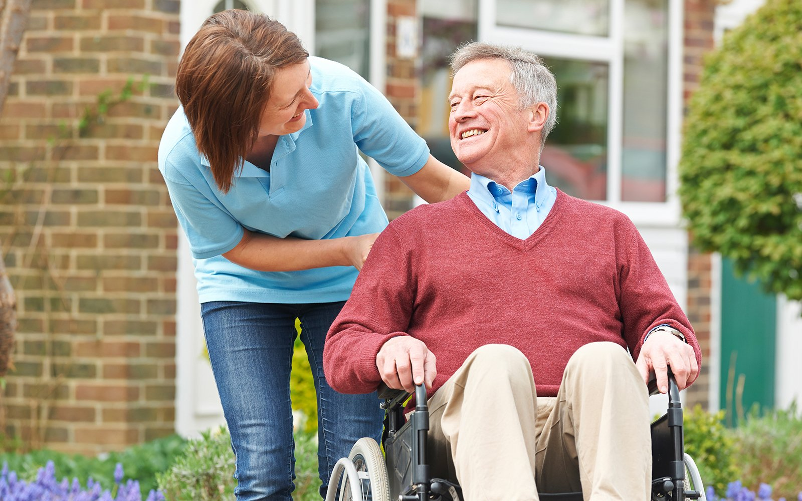 Un anziano sulla sedia a rotelle sorride alla ragazza che lo accompagna