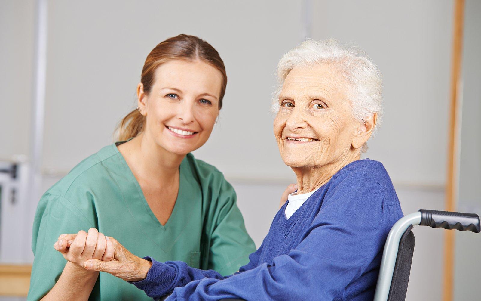 Anziana sulla sedia a rotelle sorridente con infermiera