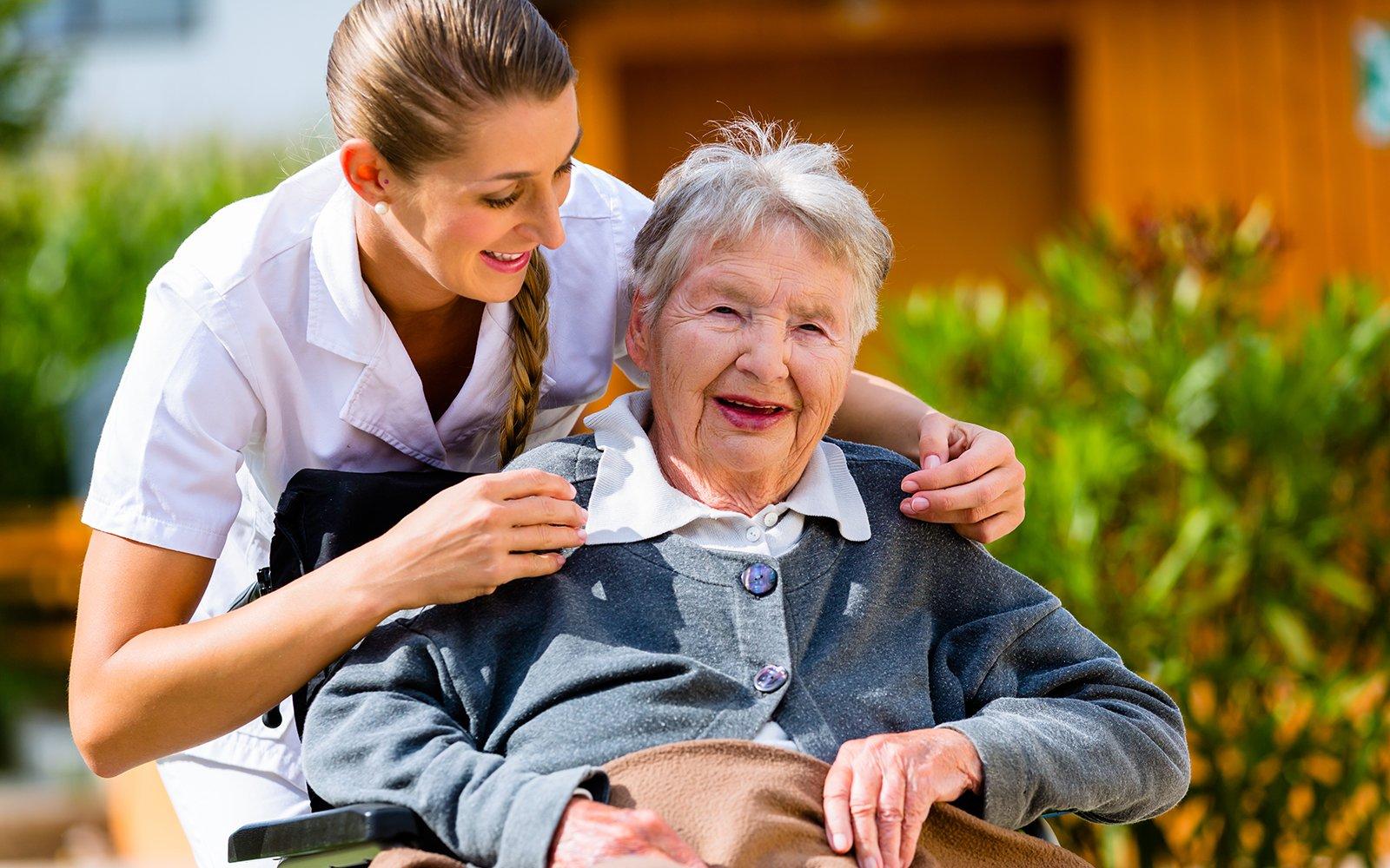 Anziana seduta sorridente con infermiera