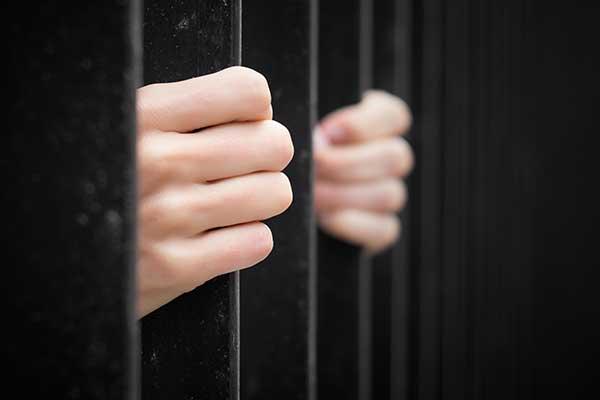 Prisoner behind jail bars