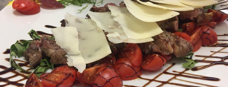 tagliata di carne con pomodorini aceto balsamico e scaglie di grana