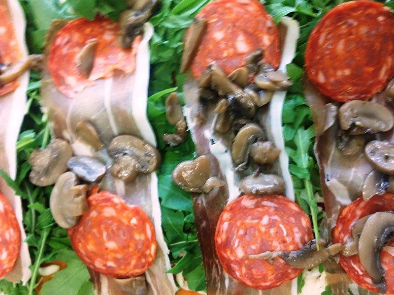 Rucola, fette di salumi e funghi porcini