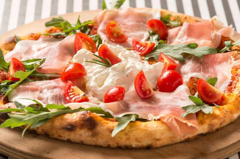una pizza con prosciutto e dei pomodorini