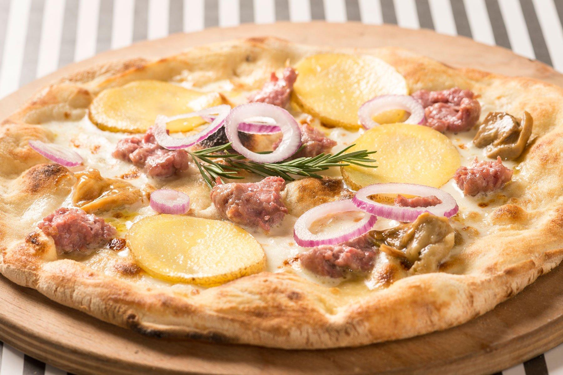 una pizza con salsiccia, funghi e patate