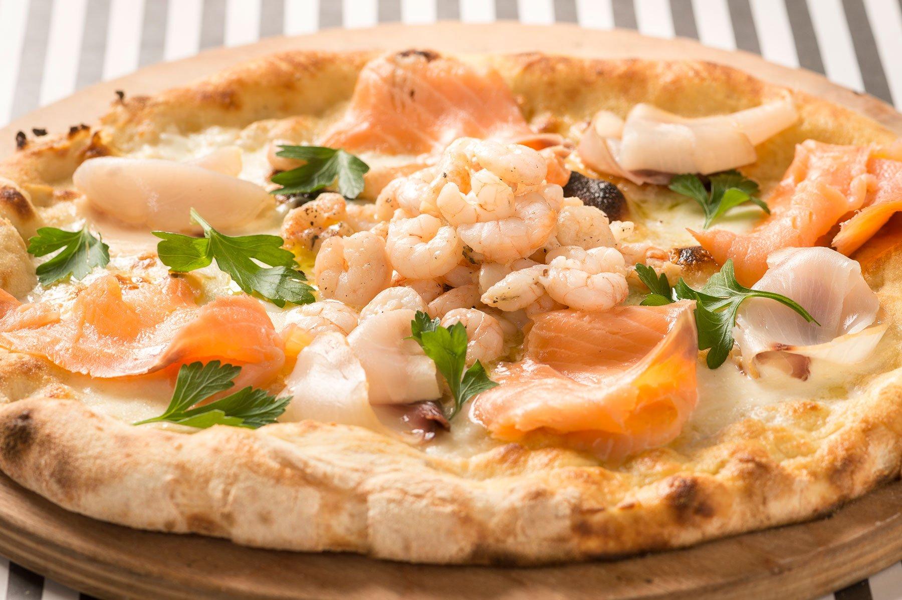 una pizza con salmone e gamberi