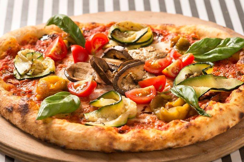 una pizza con zucchine, pomodorini e funghi