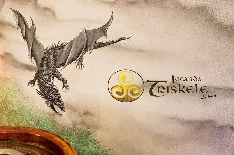 un'immagine di un drago sulla sinistra e una scritta Locanda Triskele