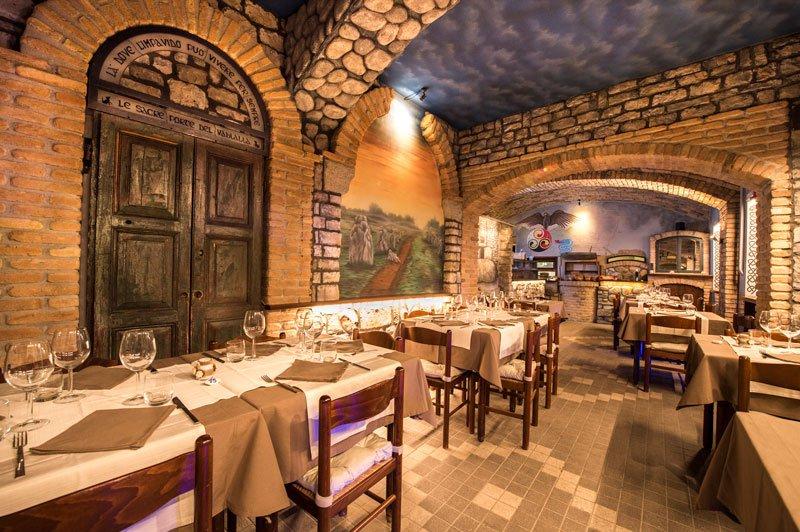tavoli apparecchiati all'interno di un ristorante con muri con mattoni a vista e dei dipinti sul puro