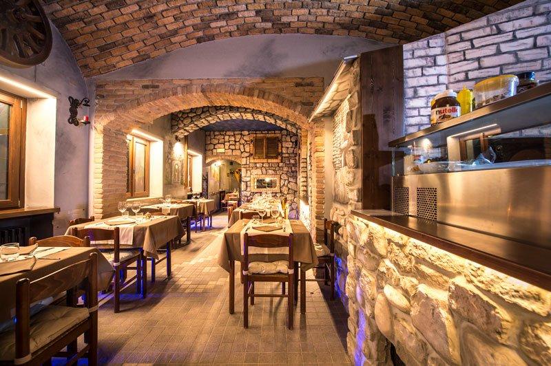 tavoli apparecchiati all'interno di un ristorante e luci blu accese