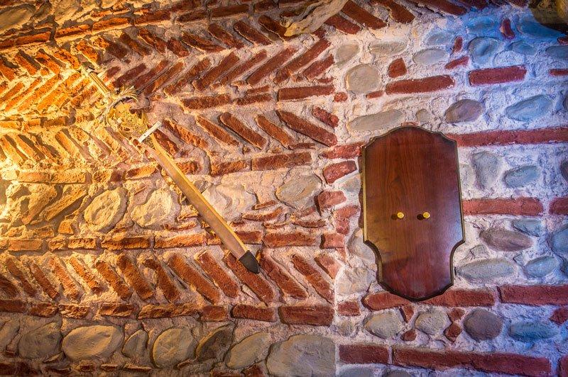 Una spada e uno scudo appesi su un muro