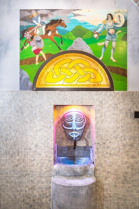 Un dipinto di due guerrieri e un cavallo appeso al muro e una sotto una fontana