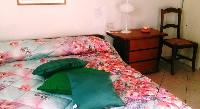 Una camera da letto con letto matrimoniale con lenzuolo di color rosa, cuscini verdi e sulla destra un comodino e un sedia in legno