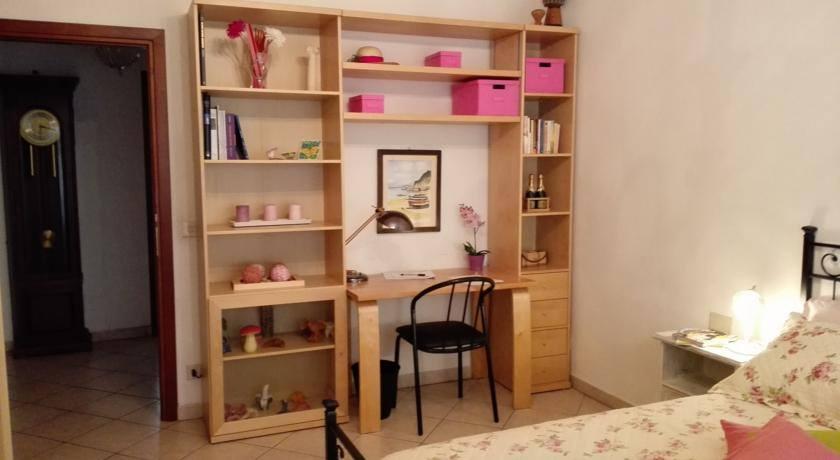 Una camera con letto in ferro battuto, una libreria con oggetti di color rosa, dei libri e una scrivania