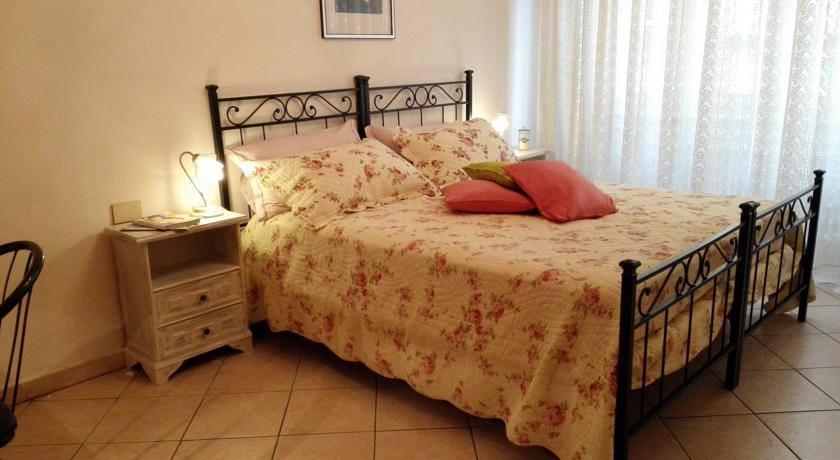 Un letto matrimoniale in ferro battuto e copriletto con fiori di color rosa, comodini di color bianco con lampade